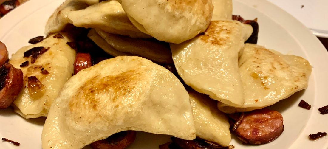 Perogies piled on a plate with shallots and sausage.